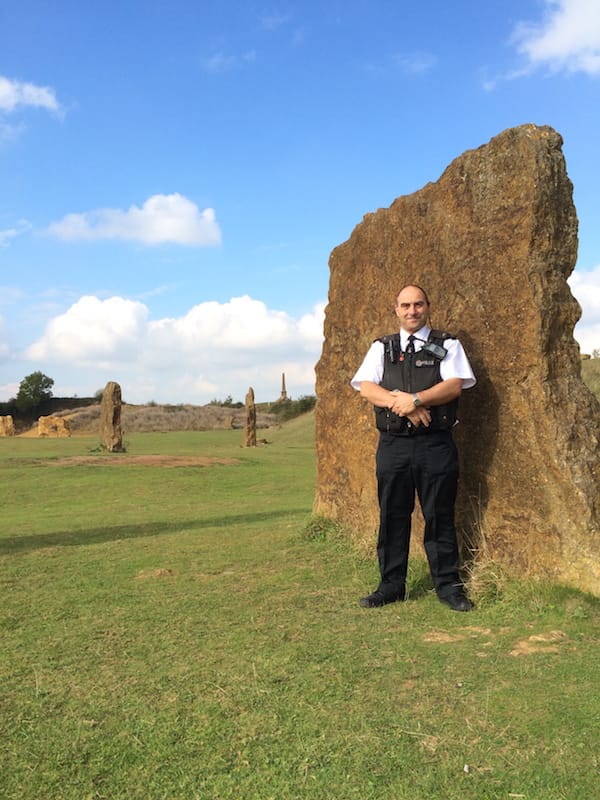 Andy Stuart in his police uniform leaning on a large upright stone from Ham Hill Stone Circle
