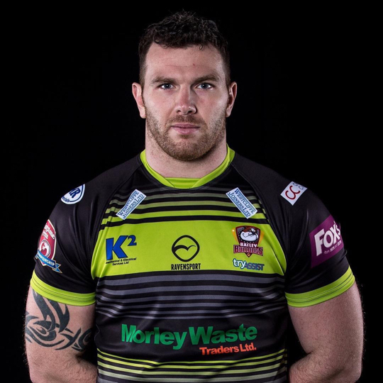 Keegan Hirst stands againsts a black background, arms behind his back, wearing his rugby uniform.