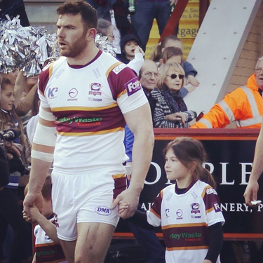 Hirst walking on a rugby field while holding two children's hands. They are wearing matching uniforms.